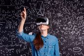 Beautiful woman in blue denim shirt wearing virtual reality goggles, pointing up with finger. Student against big blackboard with mathematical symbols and formulas. Studio shot on black background. poster