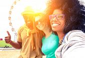 Afro hair girl taking selfie with best friends at ferris wheel at sunset - Happy multiracial group of students having fun with smartphone photo camera outside- Warm sun halo filter with vintage tones poster