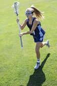 Action photo of a cute female Lacrosse player running on the grass field during a lacrosse game poster