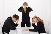 Sad Young Businesspeople With Hands On Head In Office poster
