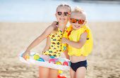 Little girl with pigtails and a little blonde boy with short hair, a brother and sister, both wearing sun glasses, a girl dressed in a yellow bathing suit and multicolored lifeline, the boy wore a yellow inflatable lifejacket, spend time together at the b poster
