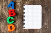 ABCD spelling from plastic letters and blank notebook on wooden background poster