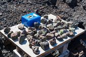 Table stall with blue till box on Canary Island with bizarre-shaped cliffs and underwater caves produced by the solidification of lava and erosion poster