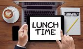 LUNCH TIME on the tablet pc screen held by businessman hands - online top view poster