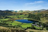 Gorgeous Watendlath valley from High Seat in the Lake District. The deep sapphire lake nestles in an emerald green vale surrounded by Lakeland Fells on a glorious sunny day under a blue sky poster