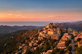The Balagne village of Speloncato in Corsica bathed in late evening sunshine with the Regino valley and Mediterranean sea behind and pink orange and deep blue skies above poster