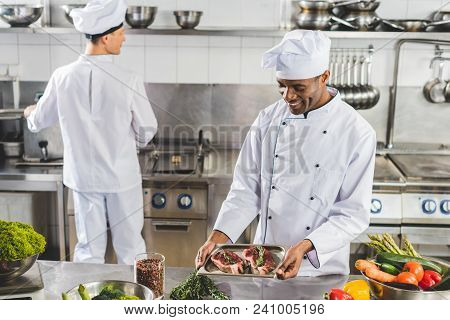 Multicultural Chefs Cooking Meat With Vegetables At Restaurant Kitchen
