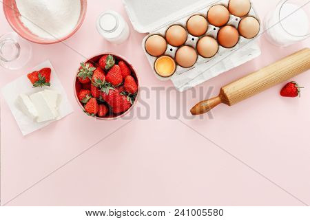 Raw Ingredients For Making Strawberry Pie Or Cake On Pink Background (eggs, Flour, Milk, Sugar, Stra