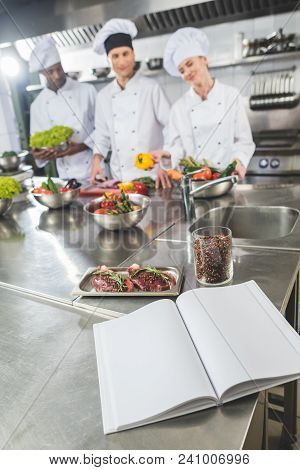 Multicultural Chefs At Restaurant Kitchen With Recipe Book On Foreground