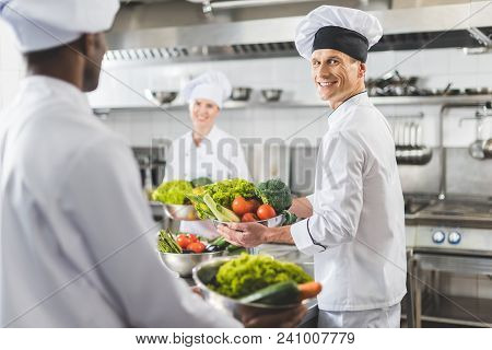 Multicultural Chefs Holding Bowls With Vegetables At Restaurant Kitchen