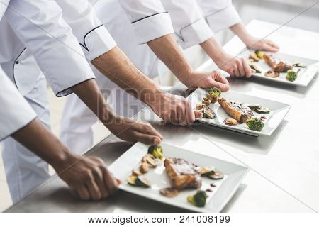 Cropped Image Of Multicultural Chefs With Plates With Steaks At Restaurant Kitchen