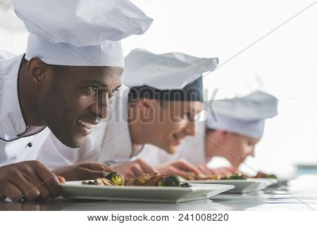 Smiling Multicultural Chefs Sniffing Cooked Food At Restaurant Kitchen