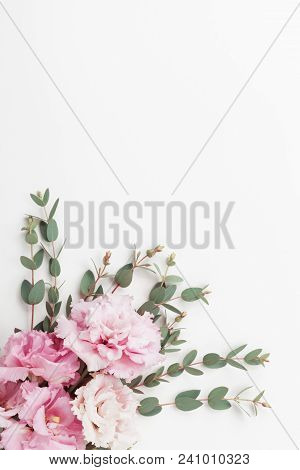 Pastel Flowers And Eucalyptus Leaves On White Table Top View. Flat Lay Style.