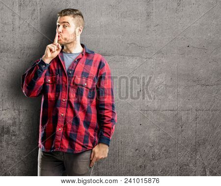 Young handsome man with index finger on lips, ask to be quiet. Silence and secret concept