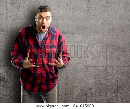 Young handsome man scared in shock, expressing panic and fear