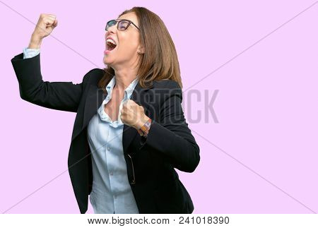 Middle age business woman happy and excited celebrating victory expressing big success, power, energy and positive emotions. Celebrates new job joyful
