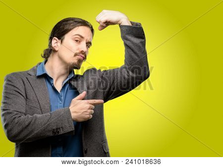 Handsome young man pointing biceps expressing strength and gym concept, healthy life its good