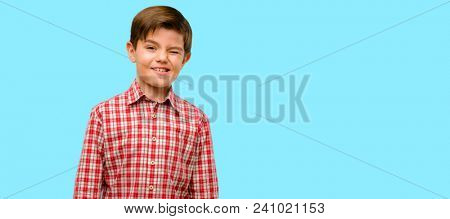 Handsome toddler child with green eyes blinking eyes with happy gesture over blue background