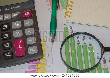 Analyzing Financial Data And Counting On Calculator. Sales Report Analysis With Pen And Calculator