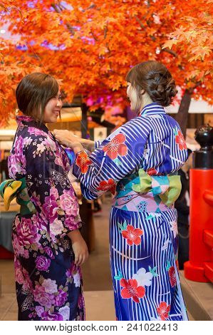 Young Woman Wearing Japanese Traditional Kimono In Autumn Color With Red Wood Bridge. Japan