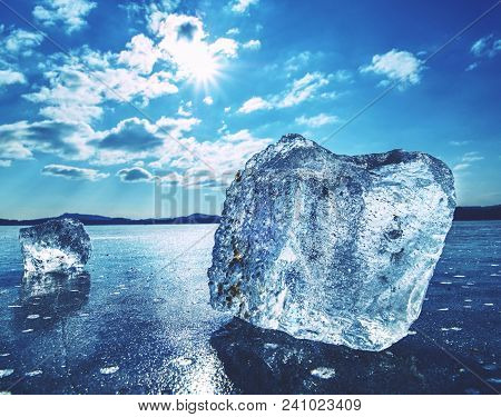 Ice Floe At Frozen Surface With Many Reflection, Blue Sky In Background. Winter Frozen Lake
