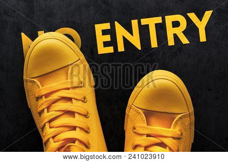 Rebellious Young Person Standing On No Entry Sign, Top View Of Yellow Sneakers On Concrete Pavement