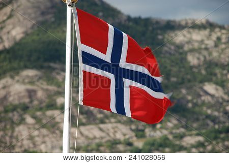 A Norwegian Flag Floating In The Wind, In The Background The Fjord Landscape Of The Lysefjord, Norwa