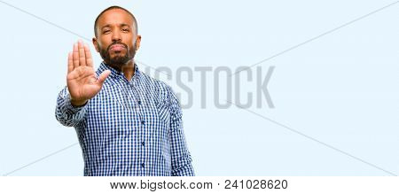 African american man with beard annoyed with bad attitude making stop sign with hand, saying no, expressing security, defense or restriction, maybe pushing isolated over blue background