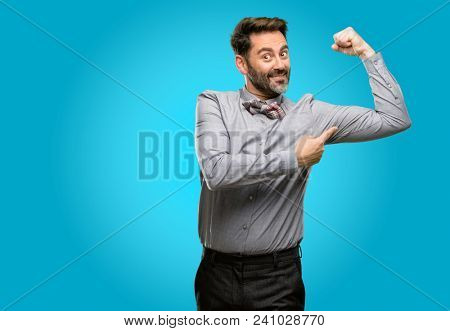 Middle age man, with beard and bow tie pointing biceps expressing strength and gym concept, healthy life its good