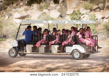 Young Schoolgirls In Pink Identical Dresses Of A School Uniform, Going On The Long Electric Vehicle