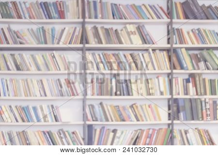 Abstract Blurred Background Of Bookshelves With Books In Public Library, Book Store, At Home, Modern