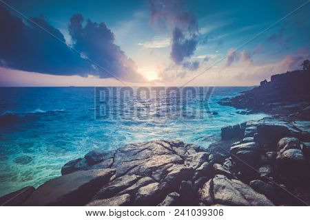 Magnificent sunset scenery the shore boulders, Indian Ocean and cloudy sky. Unawatuna, Sri Lanka. Ideal background for the various kinds of collages and illustrations in the royal blue, grey shades.