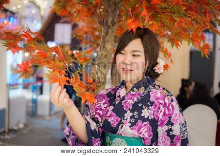 Young Woman Wearing Japanese Traditional Kimono In Autumn Color. Japan