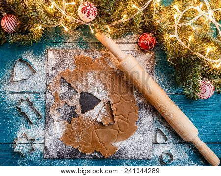 Photo Of Pine Branches, Dough, Biscuit Molds, Rolling Pin On Blue Wooden Background