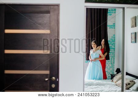 Bridesmaid Helping Bride Fasten Corset And Getting Her Dress, Preparing Bride In Morning For The Wed