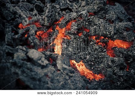 Lava Flame On Black Ash Background. Magma Textured Molten Rock Surface. Volcano, Fire, Crust. Danger