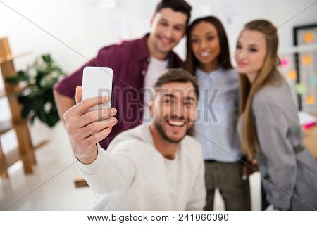 Selective Focus Of Happy Multicultural Business People Taking Selfie On Smartphone Together In Offic