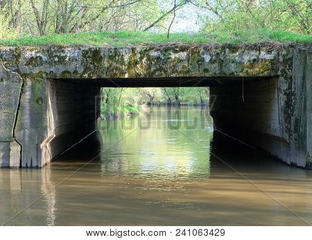 View Of The River With A Bridge And A Shore Covered With May Greenery. Spring Landscape Of The Shore