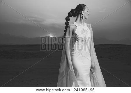 Woman In Wedding Dress And Veil. Girl Posing On Desert Sunset. Bride In Sand Dunes On Mountain Lands