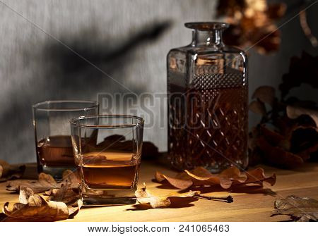 Glasses Of Whiskey On An Oak Table With Dry Oak Leaves.