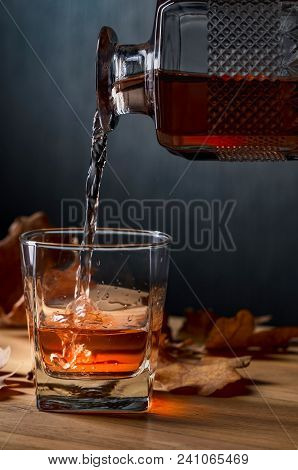 Glass Of Whiskey On An Oak Table With Dry Oak Leaves. Whiskey Is Poured Into A Glass From A Carafe.