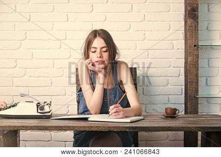 Girl Writing With Pencil In Notebook. Young Woman Sitting At Wooden Table. Teenager Student In Jean
