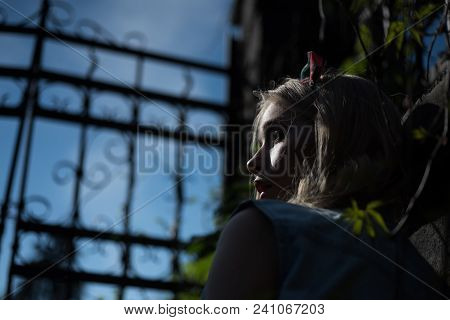 Side View Frightened Girl Wearing Headband Standing Behind Tall Gate At Dusk. Pretty Young Lady With