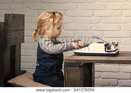 Business Kid. Small Businessman Child Sitting At Table And Typing Typewriter On White Brick Wall Bac
