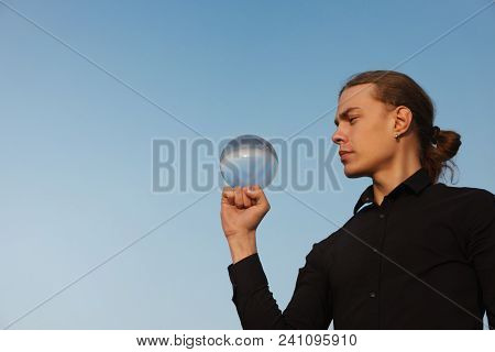 Contact Juggling. Guy Balances With Glass Ball On His Fist. Reflection Of Sky In Ball. Skill Perform