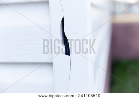 Horizontal Image Of A Big Hole Damage To The White Vinyl Siding At The Corner Of The House Exterior.