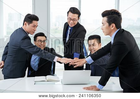 Ambitious Team Of White Collar Workers Joining Hands Together While Having Productive Working Meetin