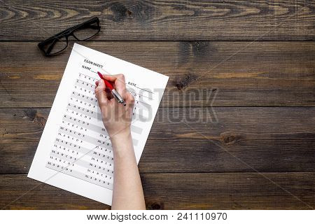 Take The Exam, Write The Exam. Hand With Pen Near Exam Paper On Dark Wooden Background Top View .