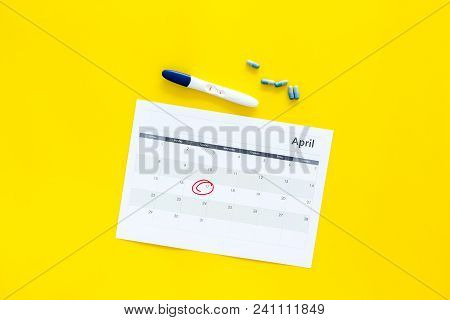 Planning Pregnancy. Positive Pregnancy Test Near Calendar Page And Pills On Yellow Background Top Vi
