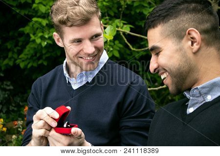Two Gay Men Dressed In Shirt And Sweaters Getting Engaged As One Man Proposes By Presenting An Engag